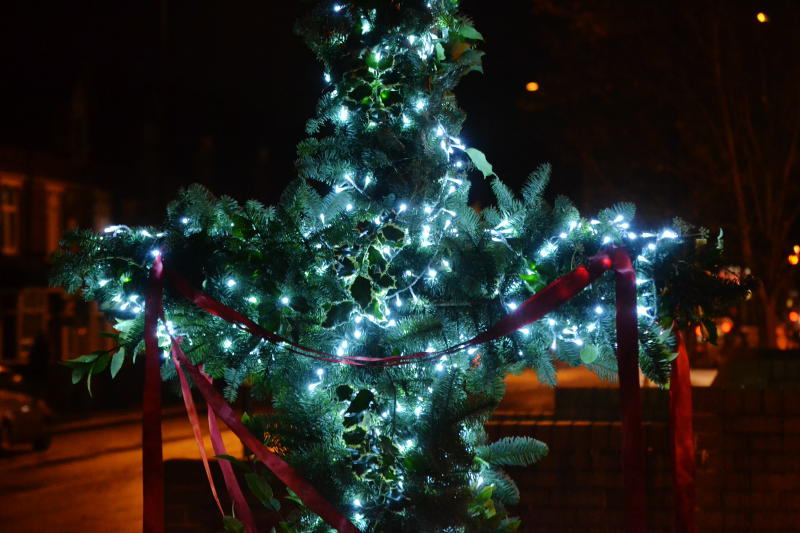 The centre of the cross outside the Christ Church building, decorated with Christmas lights and foliage